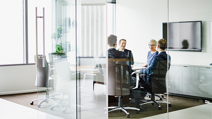 Four people in a glass-walled conference room